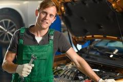 Un mecánico joven en guardapolvos verdes lleva a cabo una llave en sus manos cerca fotos de archivo libres de regalías