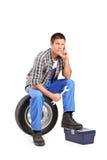 Un mecánico pensativo que se sienta en un neumático Foto de archivo
