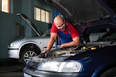 Un meccanico che controlla un veicolo Fotografie Stock