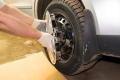 Un meccanico che rimuove il hubcap da una rotella di automobile immagini stock