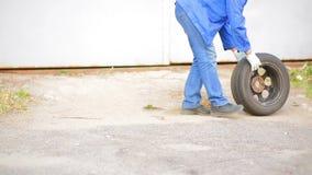 Un meccanico dell'uomo rotola sulla gomma di automobile dell'asfalto con un disco video d archivio