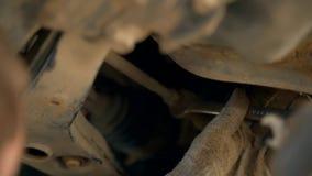 Un meccanico di automobile nel pozzo di ispezione svita il bullone sull'automobile con una chiave Adeguamento di curvatura e del  stock footage
