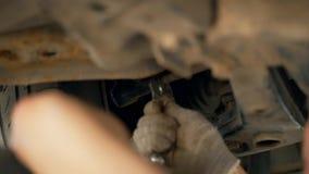 Un meccanico di automobile nel pozzo di ispezione svita il bullone sull'automobile con una chiave Adeguamento di curvatura e del  video d archivio