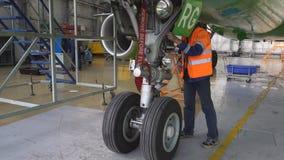 Un meccanico ispeziona l'aereo di linea anteriore del puntone 4K video d archivio