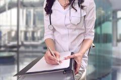 Un medico in ambulatorio realizza il lavoro amministrativo bureaucrac Fotografia Stock