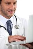 Un medico che esamina il suo computer portatile Immagini Stock