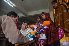 Un medico che scrive prescrizione dopo il controllo madre e del bambino fotografie stock