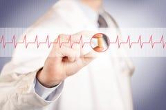 Un medico che tiene una pillola del cuore Fotografia Stock Libera da Diritti