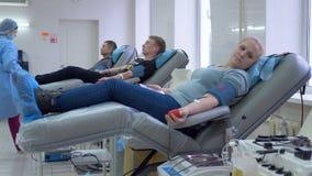 Un medico controlla i donatori di sangue in un centro di donazione, lavoro della carità archivi video