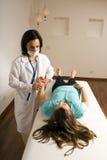 Un medico controlla la maschera impulso-Verticale del paziente Fotografia Stock
