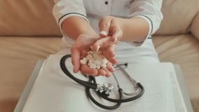 Un medico della ragazza ha versato le pillole bianche da corpo a corpo archivi video