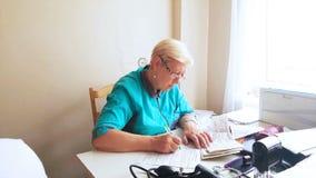 Un medico femminile è allo scrittorio e riempie le carte archivi video