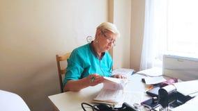 Un medico femminile è allo scrittorio e riempie le carte video d archivio