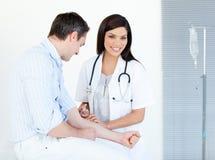 Un medico femminile che fa iniezione al suo paziente fotografia stock libera da diritti