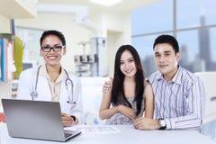 Un medico femminile con le coppie asiatiche in ambulatorio Immagine Stock