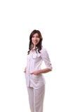 Un medico femminile con le mani in tasche dura, stando la o isolata Fotografie Stock