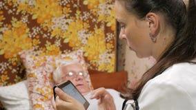 Un medico femminile interroga un paziente a casa Scrive un'anamnesi al computer della compressa video d archivio