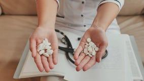 Un medico femminile nelle sue armi presenta molte pillole bianche archivi video