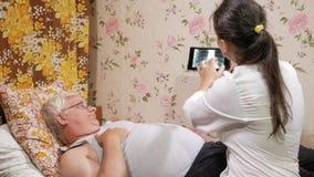 Un medico femminile visita un paziente a casa Mostra i risultati dei raggi x su un computer della compressa L'uomo sta trovandosi archivi video