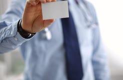 Un medico maschio sta mostrando un biglietto da visita Immagini Stock Libere da Diritti