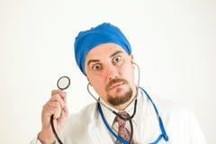 Un medico pazzo con i grandi occhi tiene uno stetoscopio e esamina la macchina fotografica fotografia stock