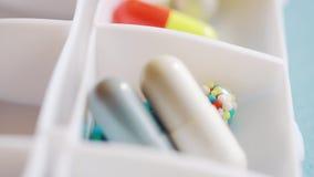 Un medico sparge fuori le pillole ed il farmaco per la settimana utilizzando nella scatola quotidiana della pillola video d archivio