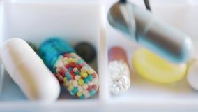 Un medico sparge fuori le pillole ed il farmaco per la settimana utilizzando nella scatola quotidiana della pillola stock footage