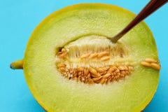 Un melón de ligamaza jugoso y una cuchara Fotografía de archivo libre de regalías