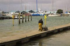 Un membro della squadra spinge un carrozzino lungo un pontone di galleggiamento al porto a Warsash nel Hampshire mentre contribui immagini stock libere da diritti