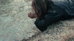 Un mendiant sans abri se trouve près de la rivière et se lave mains et le visage banque de vidéos