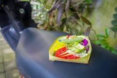 Un mercato con una scatola fatta delle foglie, dentro una disposizione dei fiori su un motorcyle, nella città di Denpasar in Indo Fotografia Stock