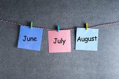 Un mese di tre estati - giugno, luglio e agosto - sulle note appuntate al fondo scuro della parete Concetto del calendario di est Fotografia Stock Libera da Diritti