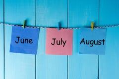 Un mese di tre estati - giugno, luglio e agosto - sulle note appuntate alla parete di legno Concetto del calendario di estate Fotografia Stock