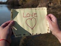 Un message d'amour de lecture de personne sur une bouteille en cristal Photos libres de droits