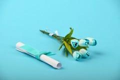 Un message de papier et fleurs sur le fond bleu Photos stock