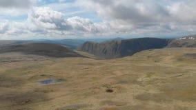 Un metraggio di andata aereo di un plateau scozzese della sommit? con la scogliera enorme nei precedenti stock footage