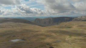 Un metraggio a rovescio aereo di un plateau scozzese della sommità con la scogliera enorme nei precedenti archivi video