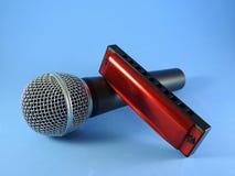 Un micrófono dinámico y una armónica diatónica fotografía de archivo libre de regalías