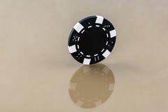 Un microprocesador negro del casino se coloca en la superficie reflectora Fotos de archivo libres de regalías