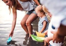 Un midsection de la familia con dos niños del niño al aire libre por el río en verano imágenes de archivo libres de regalías