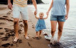 Un midsection de padres con la hija del ni?o que camina en la playa el vacaciones de verano fotos de archivo