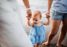Un midsection de padres con la hija del ni?o que camina en la playa el vacaciones de verano fotos de archivo libres de regalías