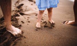 Un midsection dei genitori con la figlia del bambino che stabding sulla spiaggia sulla vacanza estiva immagini stock libere da diritti