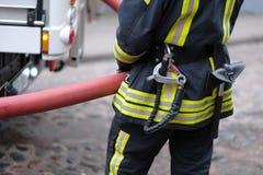 Un miembro del departamento de bomberos sostiene una manguera del abastecimiento de agua Fotografía de archivo