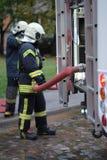 Un miembro del departamento de bomberos sostiene una manguera del abastecimiento de agua Foto de archivo
