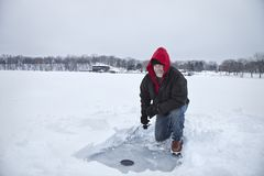 Un milieu de sourire a vieilli la glace d'homme pêchant sur un lac au Minnesota pendant l'hiver images stock