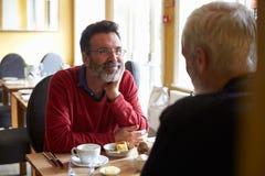 Un milieu a vieilli les couples masculins gais prenant le déjeuner dans un restaurant Image stock