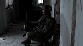Un militar con un arma ambushed en un edificio abandonado almacen de video