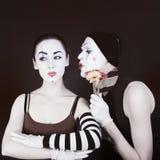 Un mimo prova a baciare una donna fotografia stock libera da diritti