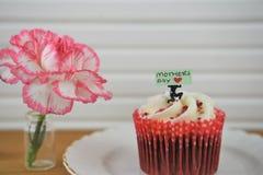 Un mini gâteau cuit au four avec la fleur fraîche d'oeillet pour le jour de mères Image stock